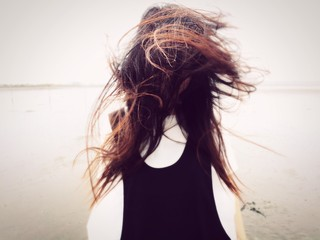 Young Woman Tossing Hair At Beach