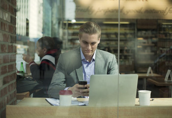 Young businessman reading smartphone texts in cafe, New York City, USA