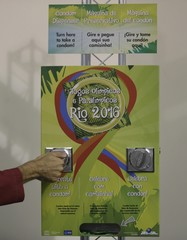 sports doctor demonstrates the operation of a condom dispenser inside the Olympic Village in Rio de Janeiro