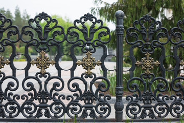 Wrought fence. Image of a decorative cast iron fence. metal fence close up. beautiful fence with artistic forging