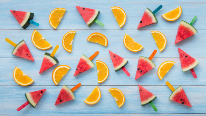 Summer concept with slices of watermelon and orange on blue rustic wooden board background