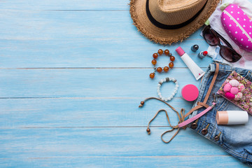 Summer concept with women's casual summer clothes with accessories items on blue rustic wooden board background