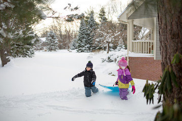 Young girl and boy, playing outdoors, in snow, pulling sled,  beside house