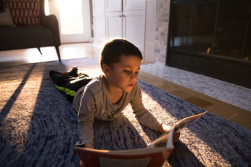 Boy reading a book while lying on floor