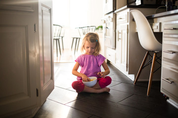 Girl eating snack while sitting in the kitchen