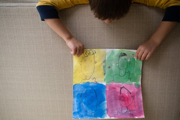 Young boy leaning over sofa, holding artwork, showing different emotions