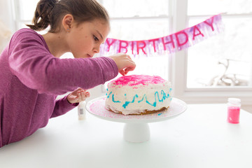 Girl decorating birthday cake with sprinkles