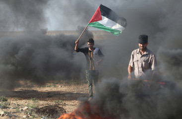 A protester holds a Palestinian flag during clashes with Israeli troops at a protest against reducing power supply to Gaza, near the border with Israel in Khan Younis in the southern Gaza Strip