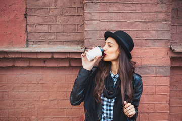 Young stylish woman in a city street drinking coffee