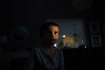 Portrait of young boy at home in dark, face illuminated by light