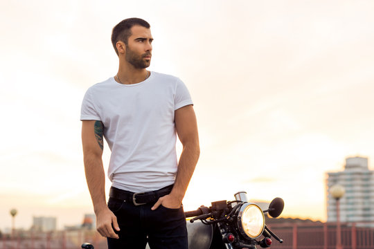 Sporty biker handsome rider male in white blank t-shirt walk away from classic style cafe racer motorbike at sunset. Vintage bike custom made in garage. Brutal urban lifestyle. Outdoor portrait.