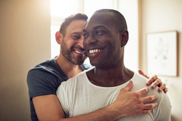 Black and white gay couple smiling and embracing gently