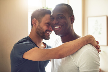 Cheerful alternative gay couple smiling and embracing together