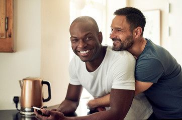 Happy multiracial gay couple with smartphone in kitchen