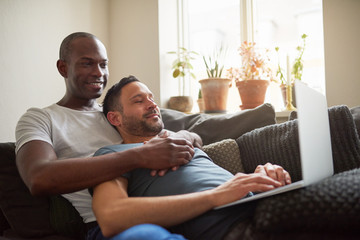 Black and white gay couple lying and browsing laptop