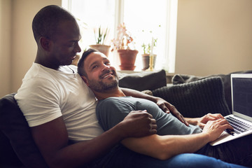 Homosexual men browsing laptop and lying on sofa