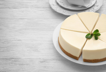 Fototapete - Plate with delicious sliced cheesecake on table