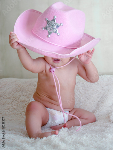 c9b2ee27787cd baby in a pink cowboy hat sitting in diapers on the couch