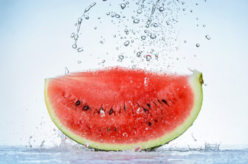 Fresh red watermelon slice with splash and drops of water