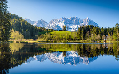 Idyllic alpine scenery, snowy mountains mirroring in a small lake, Kitzbühel, Tyrol, Austria Wall mural