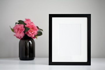 Mock up black photo frame on a white desktop next to a fresh bunch of pink camellia flowers in a black vase.