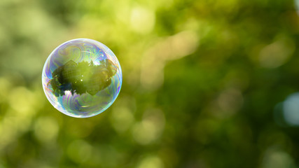 House reflection in soap bubble on green, blurred background.