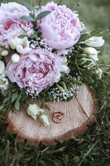 wedding rings on wood with flowers