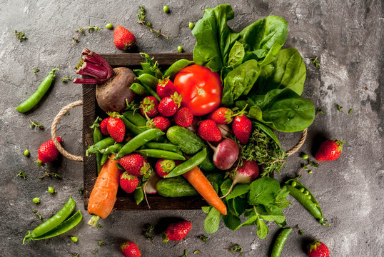 Market. Healthy vegan food. Fresh vegetables, berries, greens and fruits in wooden tray: spinach mint thyme strawberry carrots beets cucumbers radish green peas. On gray table. Copy space top view