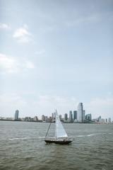 sailboat in front of manhatten skyline