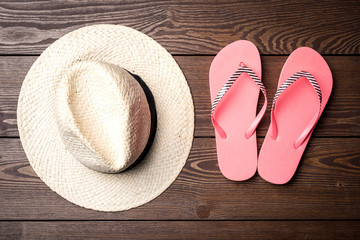 Straw hat and summer accessories on wooden table. Top view