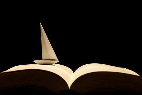 Barco de papel navegando por libro