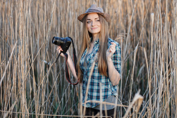 Attractive young blonde woman in blue plaid shirt straw hat enjoying her time taking photos on wild bush hard sun.