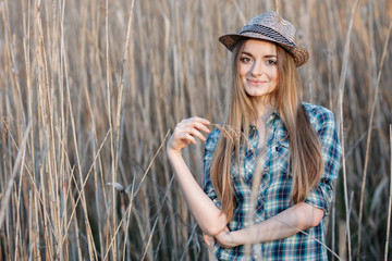 Attractive young blonde woman in blue plaid shirt straw hat enjoying her time on wild bush hard noon sun.