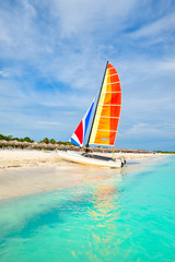 Fototapete - The beautiful beach of Varadero in Cuba with a colorful sailboat