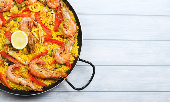 From above paella dish in a pot containing rice and vegetables with seafood. Copy space.