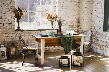 Coziness at home. Modern interior design. Beautiful vintage dining table with flowers, candles and laying near the window. Loft, botanic, rustic style. Table set for an event, party, date or wedding. Wall mural