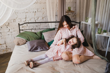 Mother and daughter hugging and playing together. Pretty little girl on beautiful woman's lap. Girls in pink dresses playing in decorated room. Family weekend, beauty day, having fun, love concept.