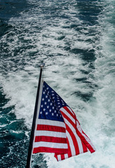 American Flag on stern of yacht against boat wake