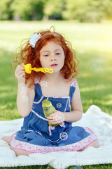 Portrait of cute funny little red-haired Caucasian girl toddler in blue dress in park outside, child blowing soap bubbles, bright summer day, lifestyle happy childhood concept