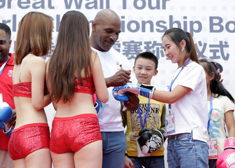 Former boxer Mike Tyson signs on a boxing glove for a woman on the outskirts of Beijing