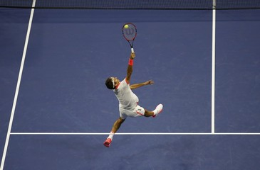 Federer of Switzerland reaches for a return against compatriot Wawrinka during their men's singles semi-final match at the U.S. Open Championships tennis tournament in New York
