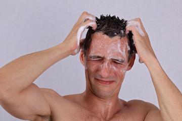 Man washing his hair, shampoo soap eye irritation