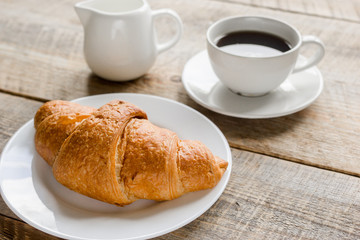 croissant and cup of coffee on office desk for business breakfast wooden background
