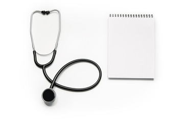 Stethoscope and prescription notepad isolated on white background. Sterile doctors office desk. Medical accessories on a white table background with copy space around products. Photo taken from above.