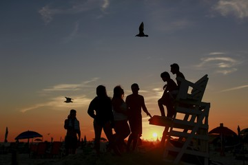 Kids are seen in silhouette at sunset on the beach in Atlantic Beach, New York,