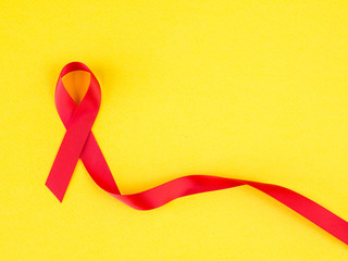 World AIDS day concept. red ribbon on yellow background.