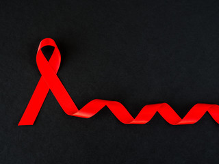 World AIDS day concept. red ribbon on black background.
