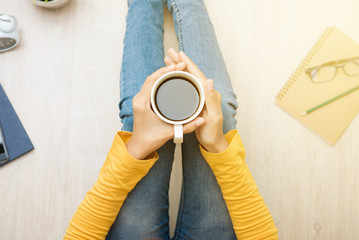 Woman sitting on the floor, holding coffee cup - top view