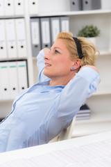 Junge blonde Mitarbeiterin macht Entspannungsübungen im Büro