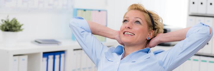 Zufriedene Mitarbeiterin im Büro Wall mural